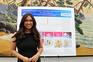 Young woman standing next to science presentation poster.